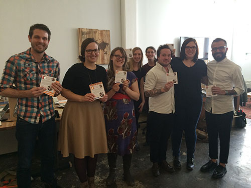 A bunch of smiling Etsy employees holding  the gifts we made for them.